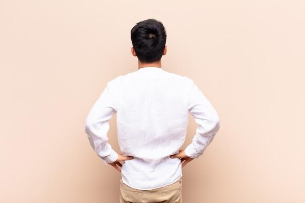 Młody człowiek czuje się zdezorientowany lub pełny lub wątpliwości i pytania, zastanawiając się, z rękami na biodrach, widok z tyłu na ścianę