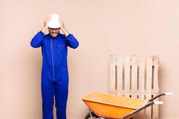 Młody człowiek czuje się zestresowany i niespokojny, przygnębiony i sfrustrowany bólem głowy, podnosząc obie ręce do koncepcji budowy głowy