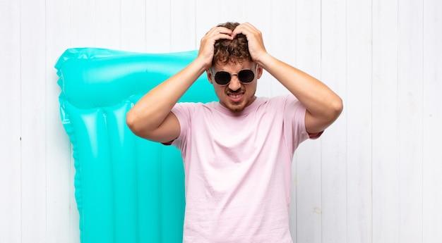 Młody człowiek czuje się zestresowany i sfrustrowany, podnosi ręce do głowy, czuje się zmęczony, nieszczęśliwy i ma migrenę. koncepcja wakacji