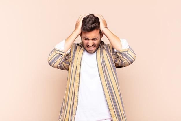 Młody człowiek czuje się zestresowany i sfrustrowany, podnosi ręce do głowy, czuje się zmęczony, nieszczęśliwy i ma migrenę