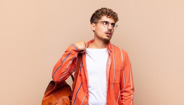Młody człowiek czuje się zestresowany, niespokojny, zmęczony i sfrustrowany, ciągnie za szyję koszuli, wygląda na sfrustrowanego problemem.