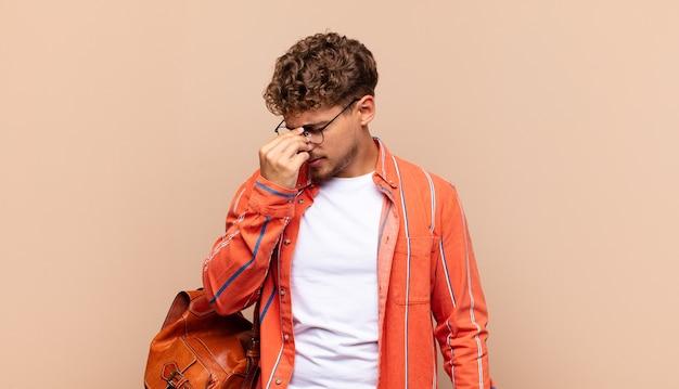 Młody człowiek czuje się zestresowany, nieszczęśliwy i sfrustrowany, dotyka czoła i cierpi na migrenę lub silny ból głowy. koncepcja studenta