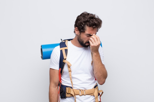 Młody człowiek czuje się zestresowany, nieszczęśliwy i sfrustrowany, dotyka czoła i cierpi na migrenę lub silny ból głowy