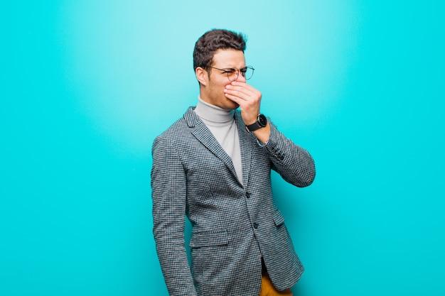 Młody człowiek czuje się zniesmaczony, trzymając nos, aby nie poczuć nieprzyjemnego i nieprzyjemnego smrodu na niebieskiej ścianie