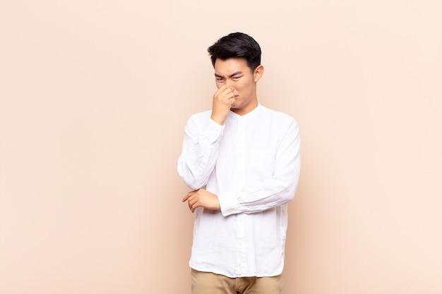 Młody człowiek czuje się zniesmaczony, trzymając nos, aby nie poczuć nieprzyjemnego i nieprzyjemnego smrodu na ścianie koloru
