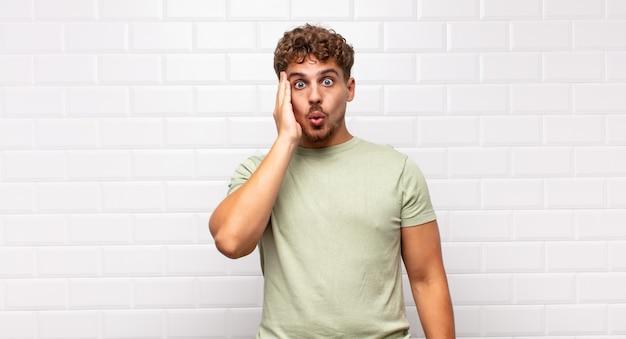 Młody człowiek czuje się zszokowany i zdziwiony, trzymając się z niedowierzaniem twarzą w twarz z szeroko otwartymi ustami