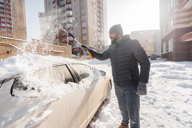 Młody człowiek czyści swój samochód po śniegu w słoneczny, mroźny dzień.