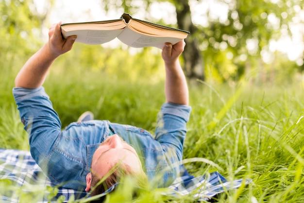 Młody człowiek czyta ciekawą książkę podczas gdy relaksujący w trawie