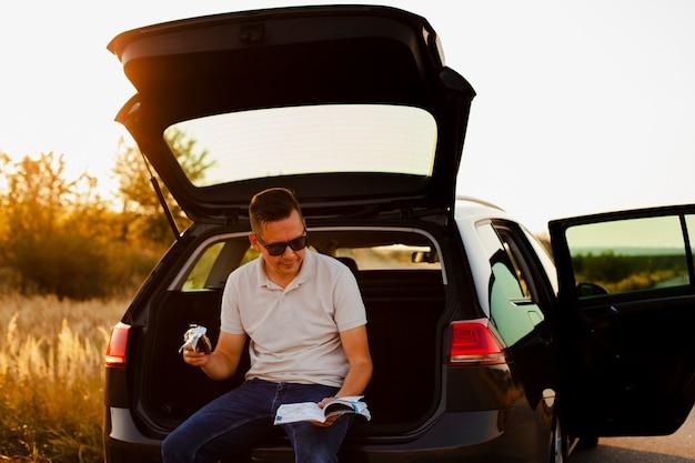 Młody człowiek czyta książkę i je czekoladę na bagażniku samochodu