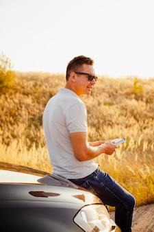 Młody człowiek czyta książkę na masce samochodu