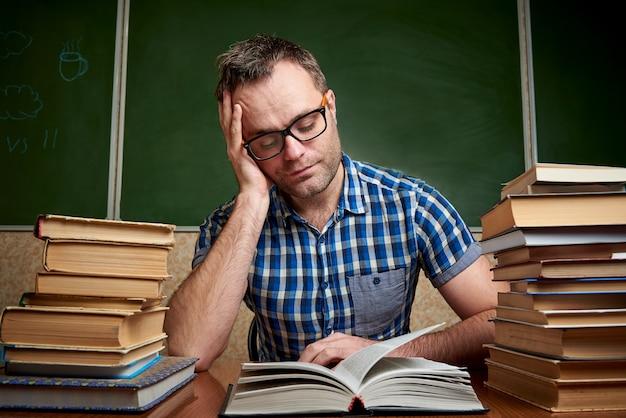 Młody człowiek czyta książkę przy stole ze stosami książek.