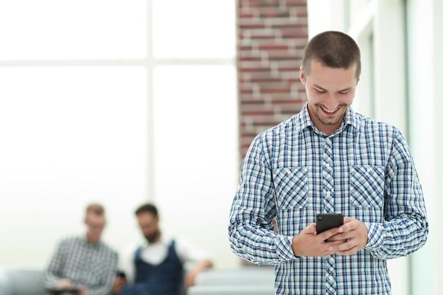 Młody człowiek czyta sms na swoim smartfonie. ludzie i technologia