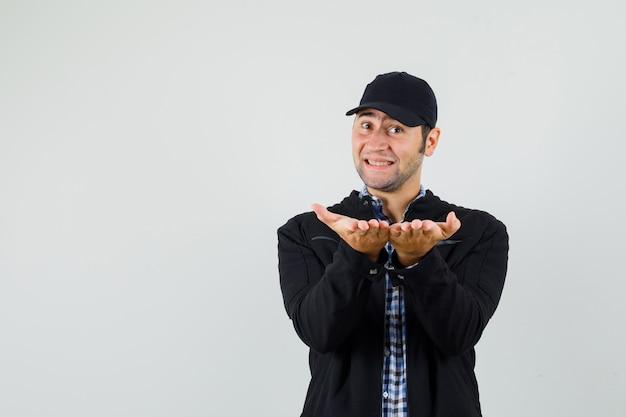 Młody człowiek dający lub odbierający gest w koszuli, kurtce, czapce i delikatny wygląd