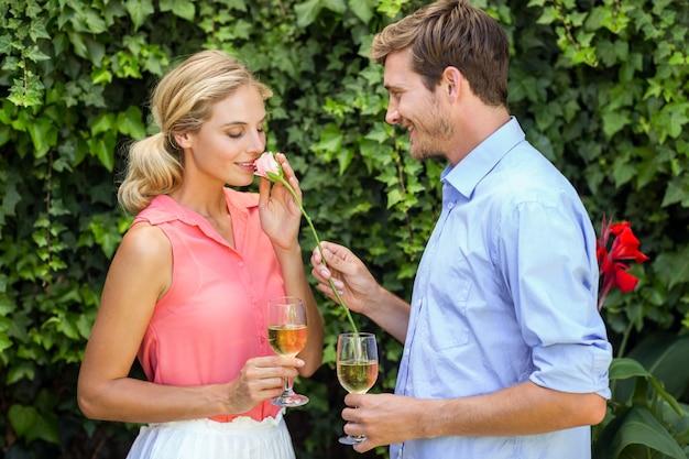 Młody człowiek daje kwiatowi kobieta podczas gdy trzymający wineglasses