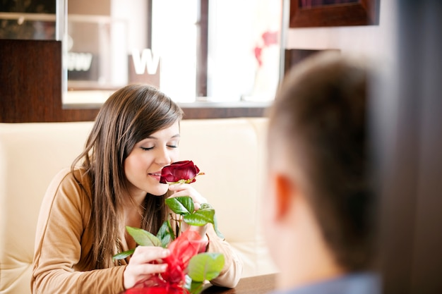 Młody człowiek daje różę swojej dziewczynie