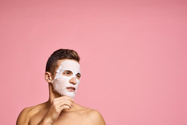 Młody człowiek dba o skórę ciała i twarzy, twarz w domu