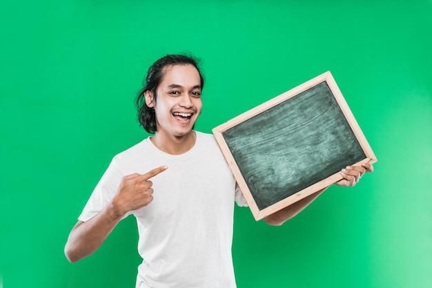 Młody człowiek długie czarne włosy trzymając i wskazując na coś na pustej tablicy na zielonej ścianie