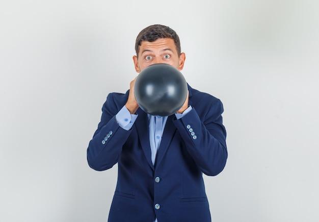 Młody człowiek dmuchanie czarny balon w garniturze