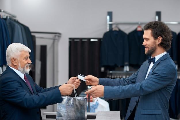Młody człowiek dokonuje zakupu i gavaing karty kredytowej.