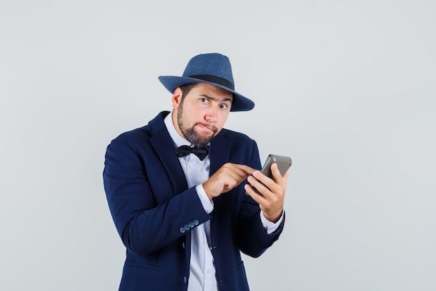 Młody człowiek dokonywanie obliczeń na kalkulatorze w garniturze, kapeluszu i patrząc przebiegły. przedni widok.