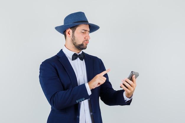 Młody człowiek dokonywanie obliczeń na kalkulatorze w garniturze, kapeluszu i patrząc skoncentrowany. przedni widok.