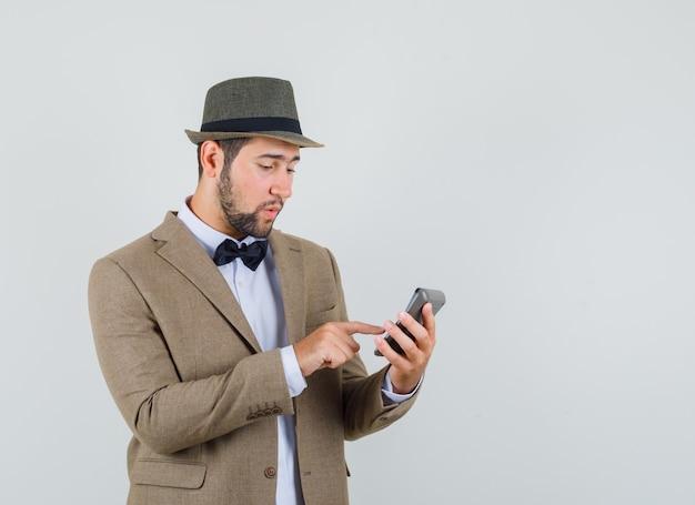 Młody człowiek dokonywanie obliczeń na kalkulatorze w garniturze, kapeluszu i patrząc zajęty. przedni widok.