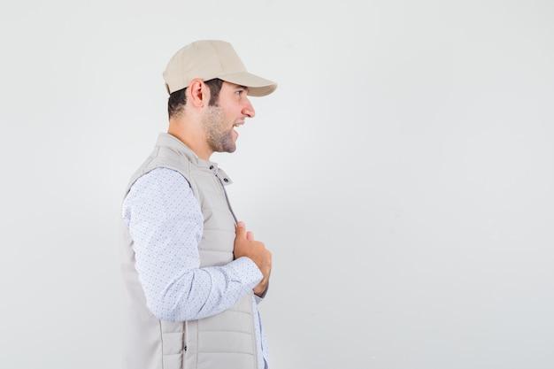 Młody człowiek dopasowując kołnierz podczas rozmowy w koszuli, kurtce bez rękawów, czapce i patrząc skoncentrowany. .