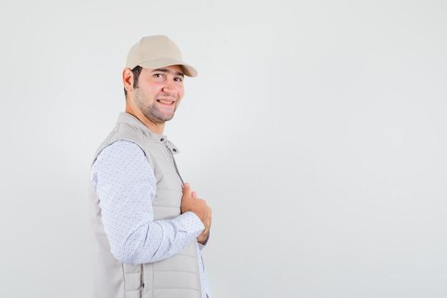 Młody człowiek, dopasowując kołnierz, uśmiechając się w koszuli, kurtce bez rękawów, czapce i patrząc zadowolony. miejsce na tekst