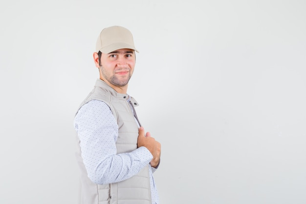 Młody człowiek dopasowując kołnierzyk w koszuli, kurtce bez rękawów, czapce i wyglądając na pewnego siebie. .