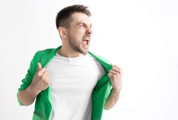 Młody człowiek dorywczo krzyczy. krzyczeć. płacz emocjonalny mężczyzna krzyczy na tle studia. portret mężczyzny w połowie długości. ludzkie emocje, koncepcja wyrazu twarzy.