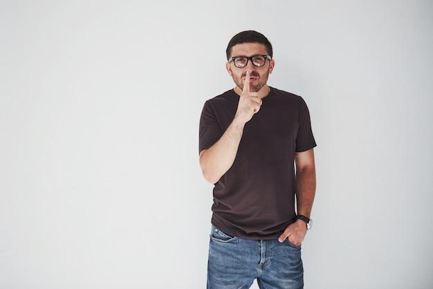 Młody człowiek dorywczo na białej ścianie, prosząc o spokój z palcem na ustach.
