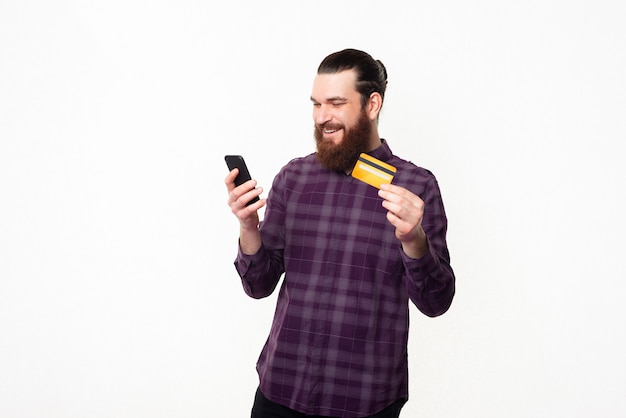 Młody człowiek dorywczo przy użyciu smartfona i karty kredytowej, bankowość internetowa