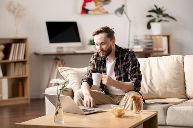Młody człowiek dorywczo z kubkiem gorącego napoju, patrząc na wyświetlacz laptopa siedząc na kanapie, oglądając wideo online i jedząc przekąskę