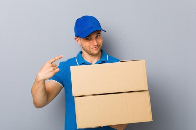 Młody człowiek dostarcza paczki wskazujące na ciebie palcem, jakby zapraszając zbliżył się.