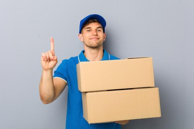 Młody człowiek dostarcza pakiety wskazujące numer jeden palcem.