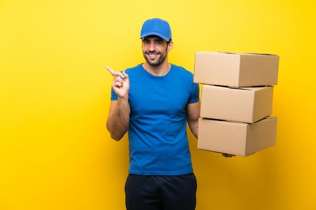 Młody człowiek dostawy na pojedyncze żółte ściany wskazujące na bok, aby przedstawić produkt