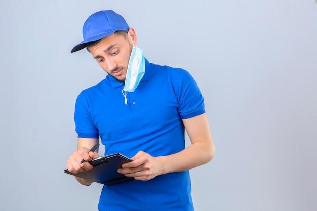 Młody człowiek dostawy na sobie niebieską koszulkę polo i czapkę z medyczną maską ochronną na uchu, sporządzanie notatek w schowku na białym tle