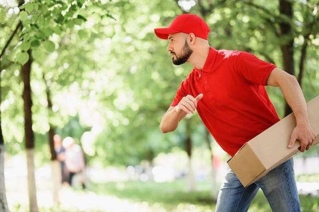 Młody człowiek dostawy niosąc karton