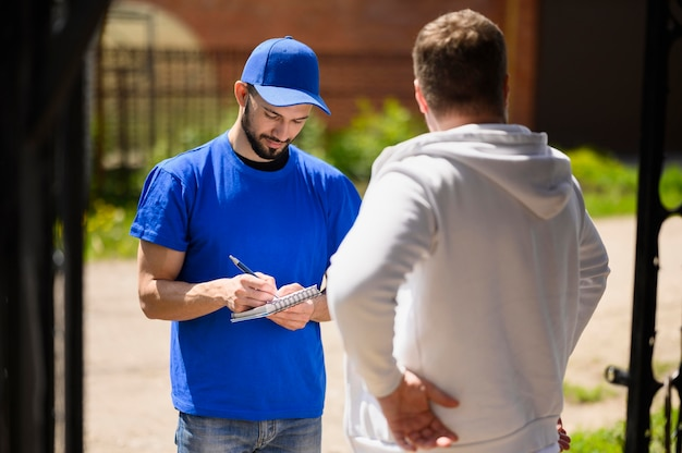 Młody człowiek dostawy podpisania do wysyłki