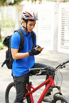 Młody człowiek dostawy sprawdzanie aplikacji w swoim telefonie