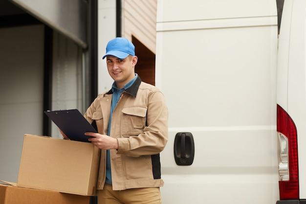 Młody człowiek dostawy sprawdzanie ładunku po dostarczeniu on stojący na zewnątrz i uśmiechając się do kamery