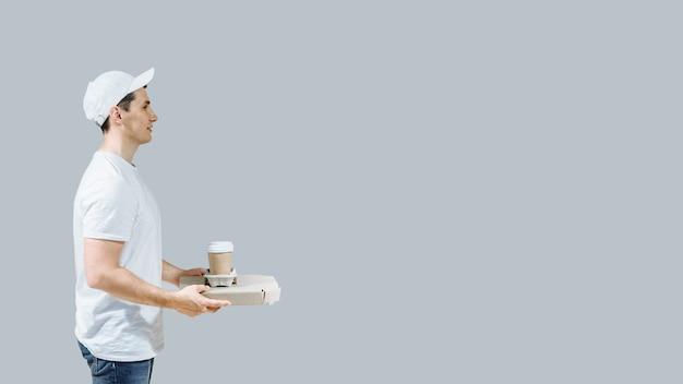 Młody człowiek dostawy, trzymając pudełka po pizzy i kawę