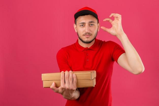 Młody człowiek dostawy ubrany w czerwoną koszulkę polo i czapkę stojącą z pudełkami po pizzy patrząc na kamery pokazujący znak rozmiaru palcami na na białym tle różowym tle