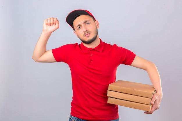 Młody człowiek dostawy ubrany w czerwoną koszulkę polo i czapkę stojącą ze stosem pudełek po pizzy pokazujący pięść do kamery agresywny wyraz twarzy na białym tle