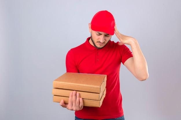 Młody człowiek dostawy ubrany w czerwoną koszulkę polo i czapkę stojącą ze stosem pudełek po pizzy wyglądający na przepracowanego dotykającego głowy cierpiącej na ból głowy na izolowanym białym tle
