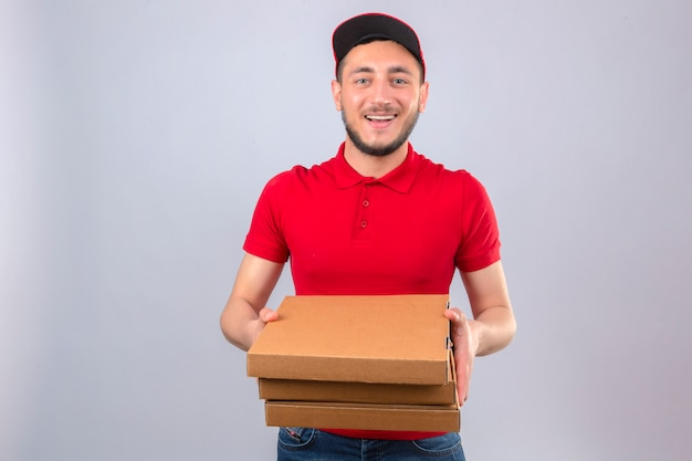 Młody człowiek dostawy ubrany w czerwoną koszulkę polo i czapkę wyciągając stos pudełek po pizzy uśmiechnięty przyjazny na pojedyncze białym tle