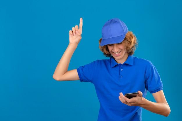 Młody człowiek dostawy ubrany w niebieską koszulkę polo i czapkę patrząc na ekran swojego smartfona, wskazując palcem wskazującym w górę nowa koncepcja pomysłu stojąca na na białym tle niebieskim tle