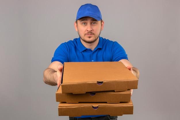 Młody człowiek dostawy ubrany w niebieską koszulkę polo i czapkę trzymając i wyciągając stos pudełek po pizzy na białym tle