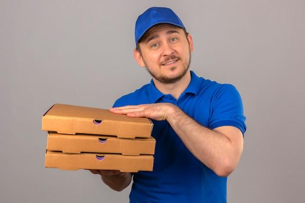 Młody człowiek dostawy ubrany w niebieską koszulkę polo i czapkę trzymając stos pudełek po pizzy patrząc na kamery uśmiechnięty przyjazny na pojedyncze białym tle