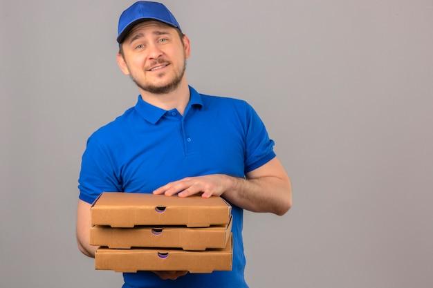 Młody człowiek dostawy ubrany w niebieską koszulkę polo i czapkę trzymając stos pudełek po pizzy patrząc na kamery z przyjaznym uśmiechem stojącym na białym tle
